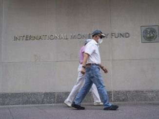 People walk past the headquarters of the International Monetary Fund (IMF) in Washington D.C., the United States, July 17, 2020. (Xinhua/Liu Jie)